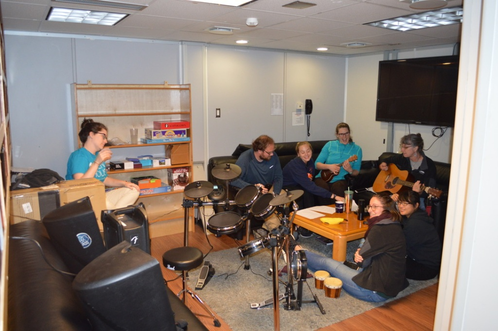 Several people sitting on couches and chairs around a coffee table. There are people holding ukuleles and guitars, and there is an electric drum set in the foreground. The people in the photo are smiling and laughing.